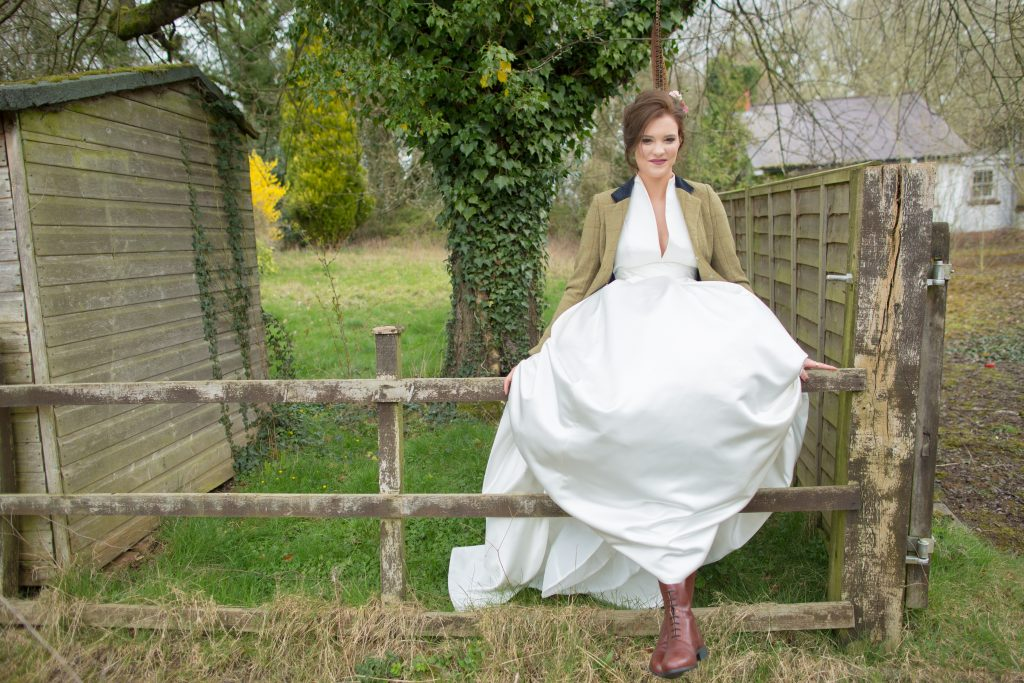 Bride wearing boots and tweed jacket sat on fence
