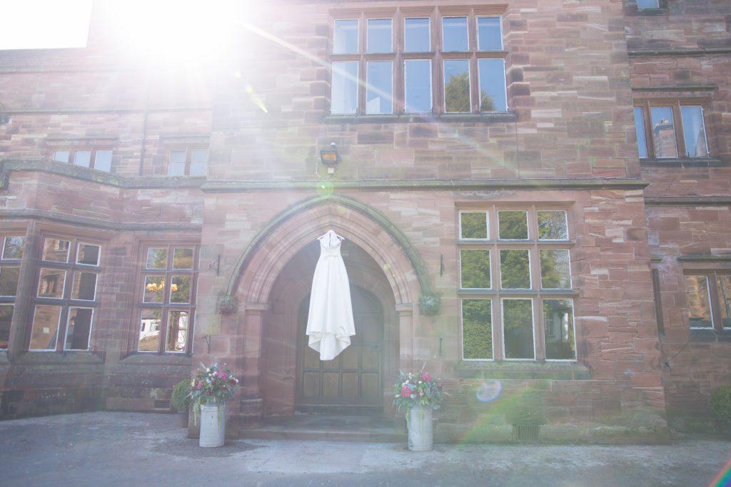 Wedding gown hanging in door way outside Standon Hall