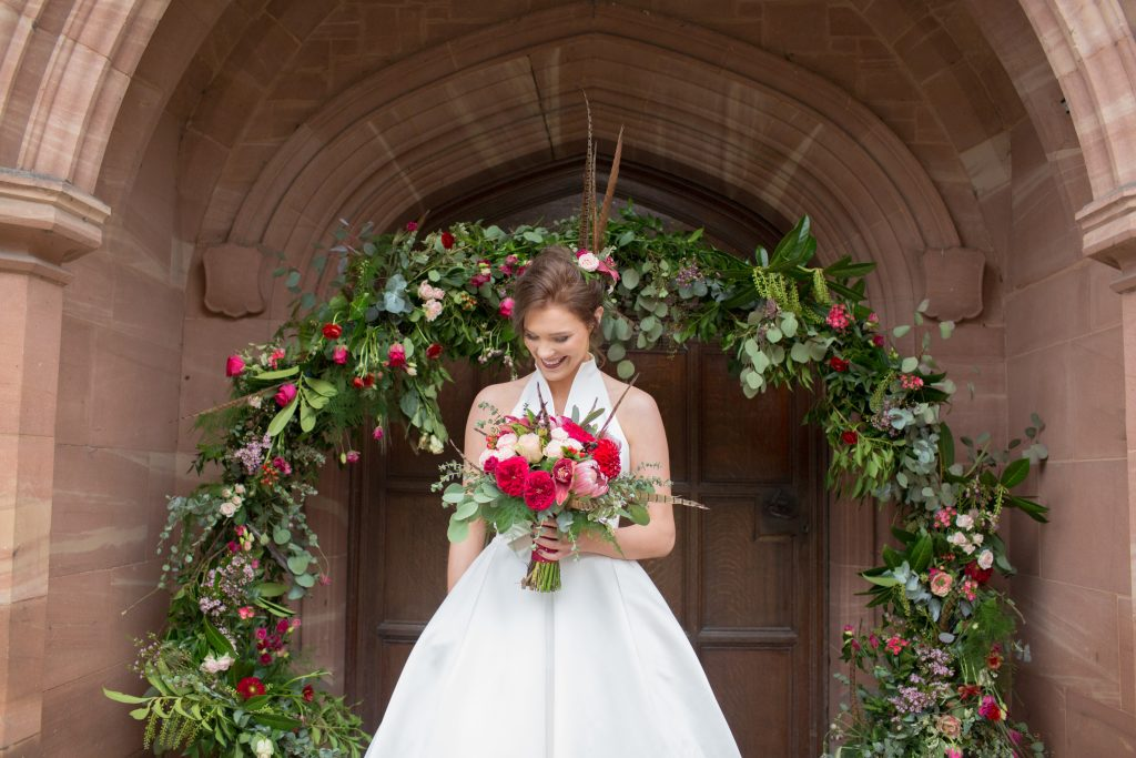 Model stood outside Standon Hall holding wedding bouquet