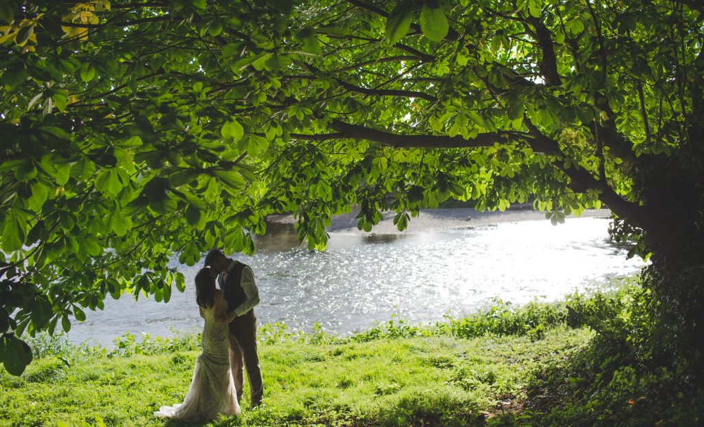 Newly weds kiss by the river