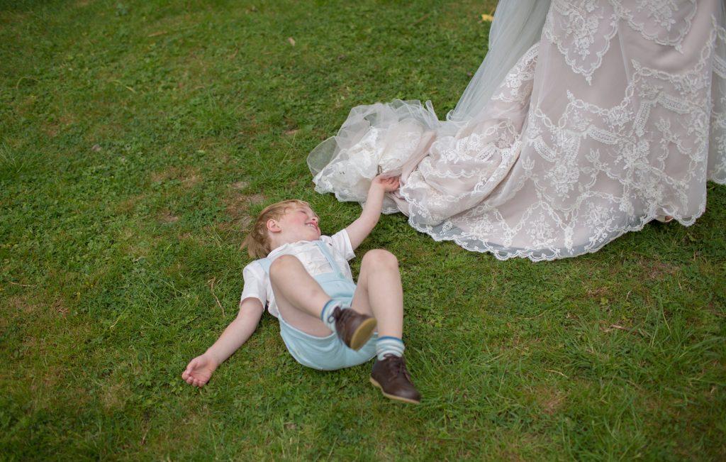 Paige boy lying on grass with wedding dress train