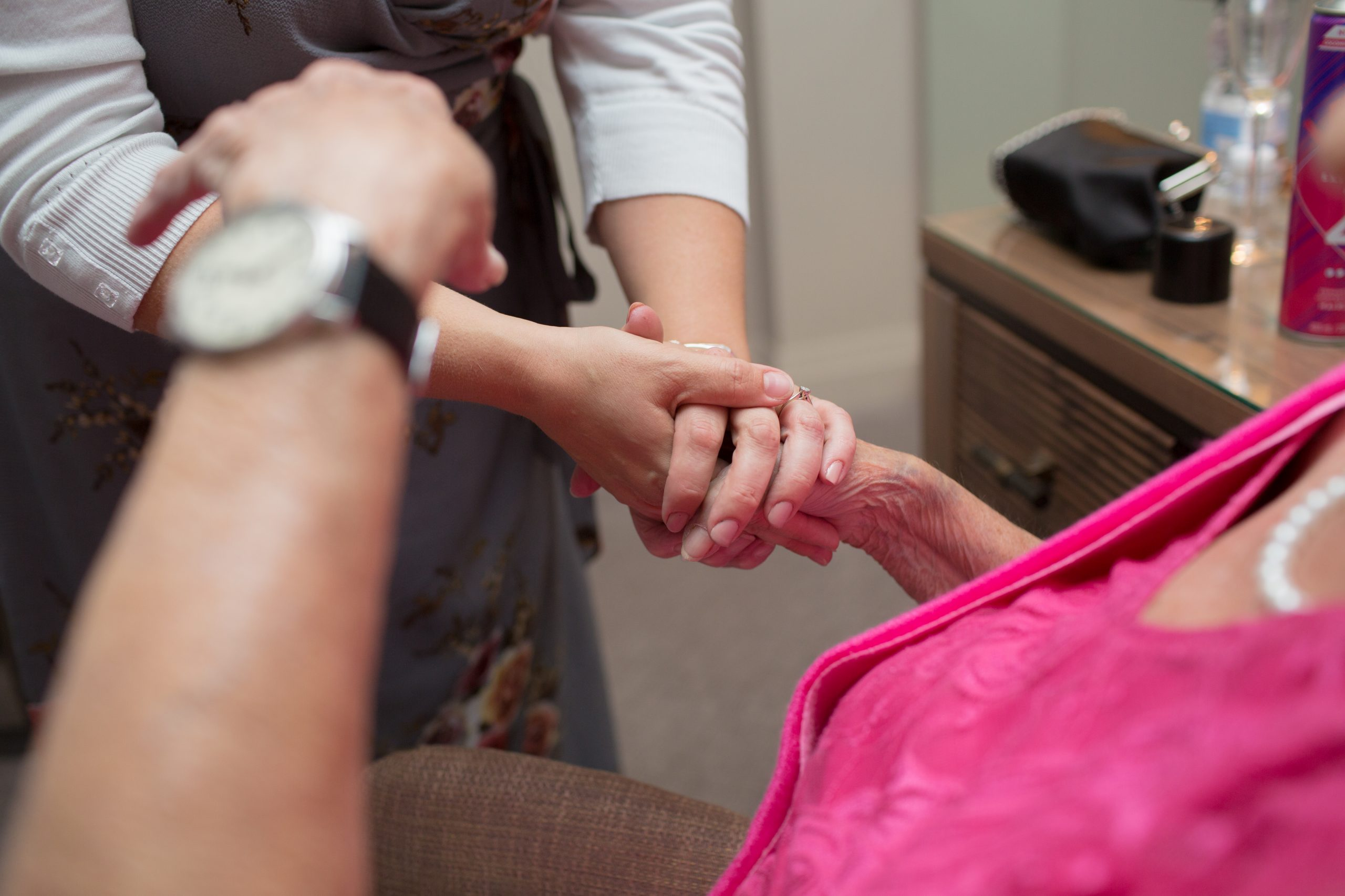 close up photo of grandma holding grand daughters hand