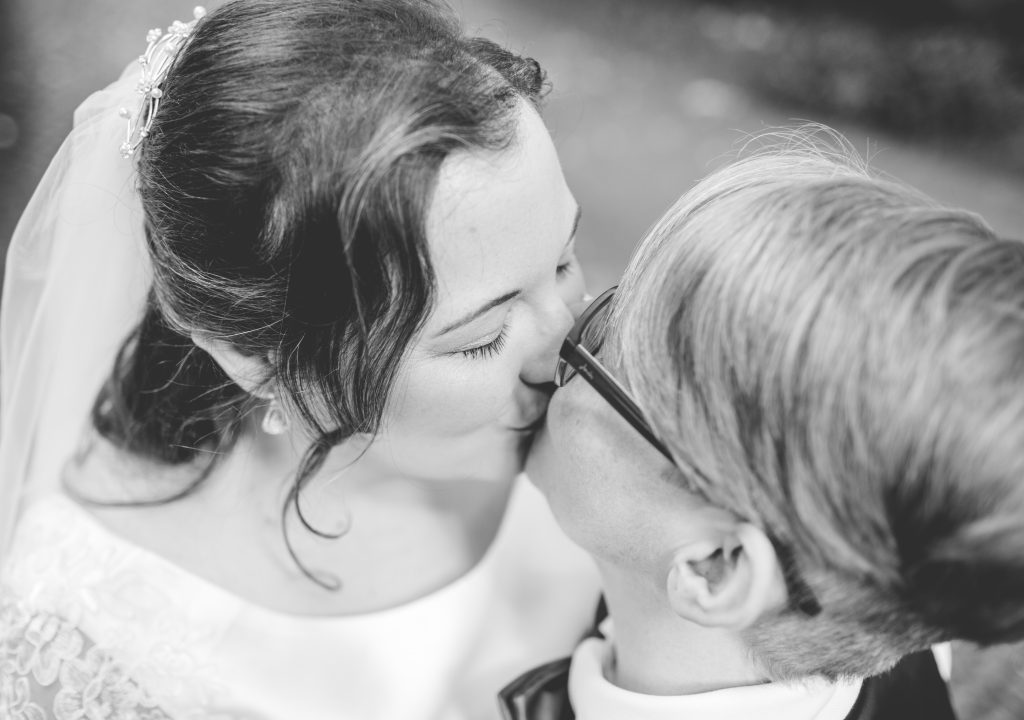 black and white photo of two brides kissing