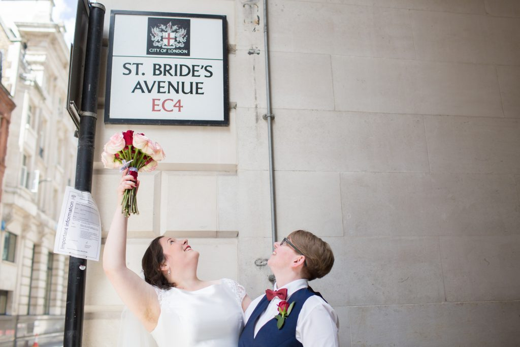 bride pointing at sign with bouquet