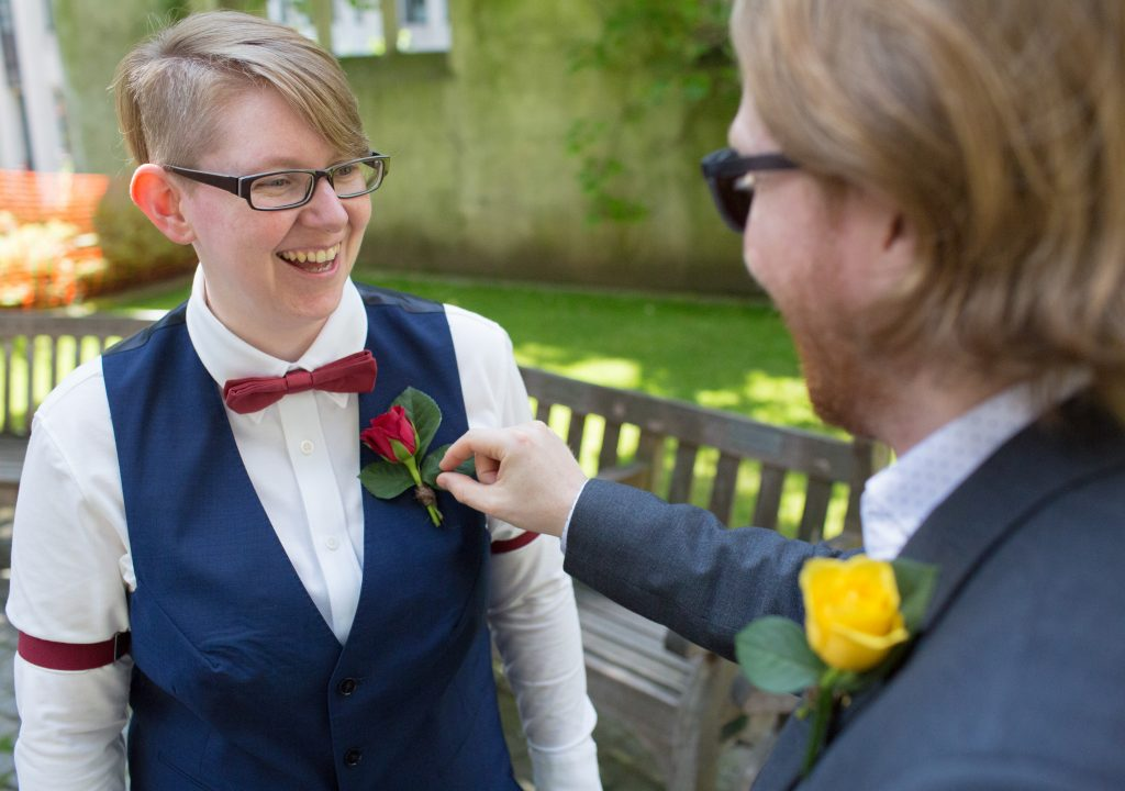 bride having buttonhole checked by best person