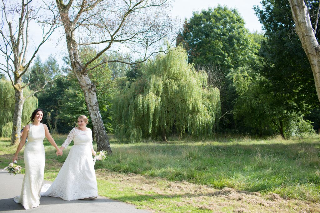 two brides on wedding day walking through park