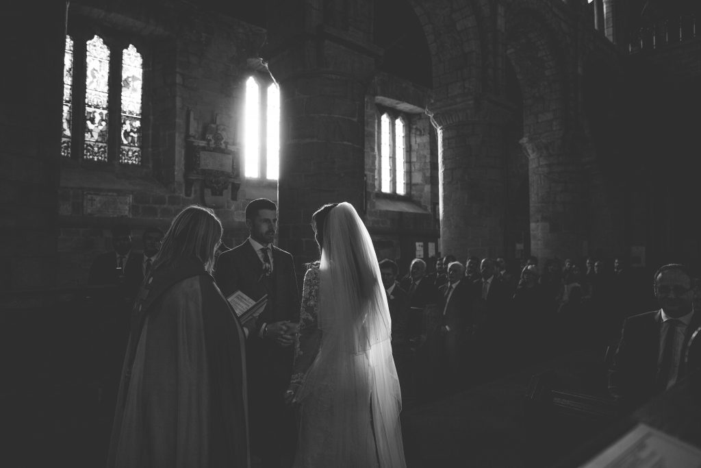 black and white photo of wedding ceremony inside a church