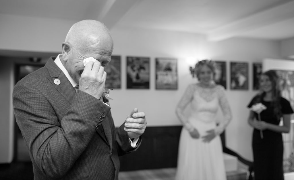 black and white photo of father of bride crying