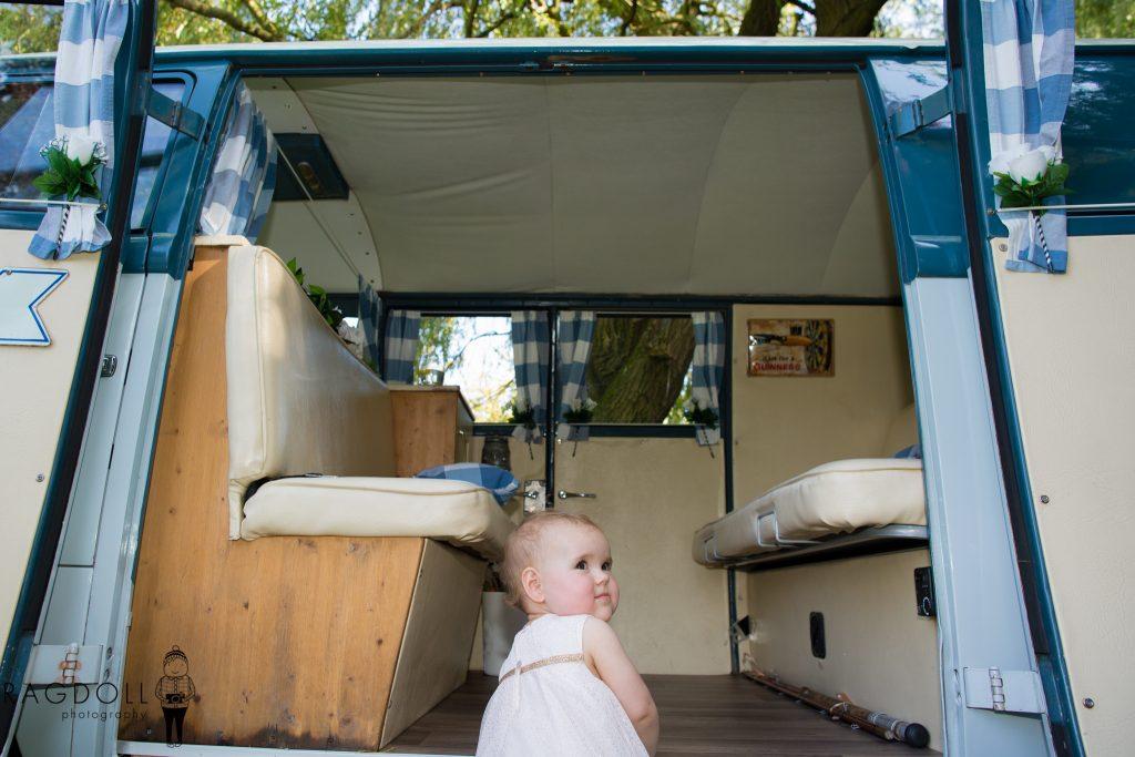 young flower girl climbing into camper van