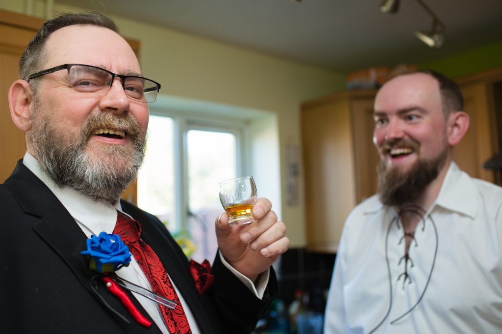 father of groom laughing with son