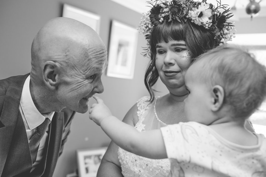 black and white photo of bride holding daughter who is pointing to a tear