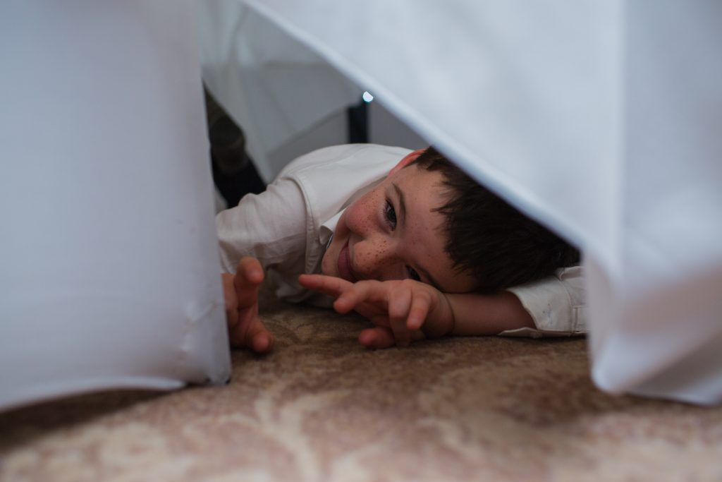 photo of young wedding guest under a table