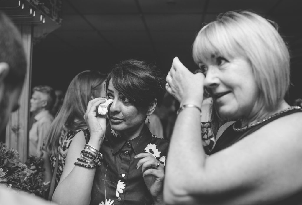 black and white photo of two wedding guests crying