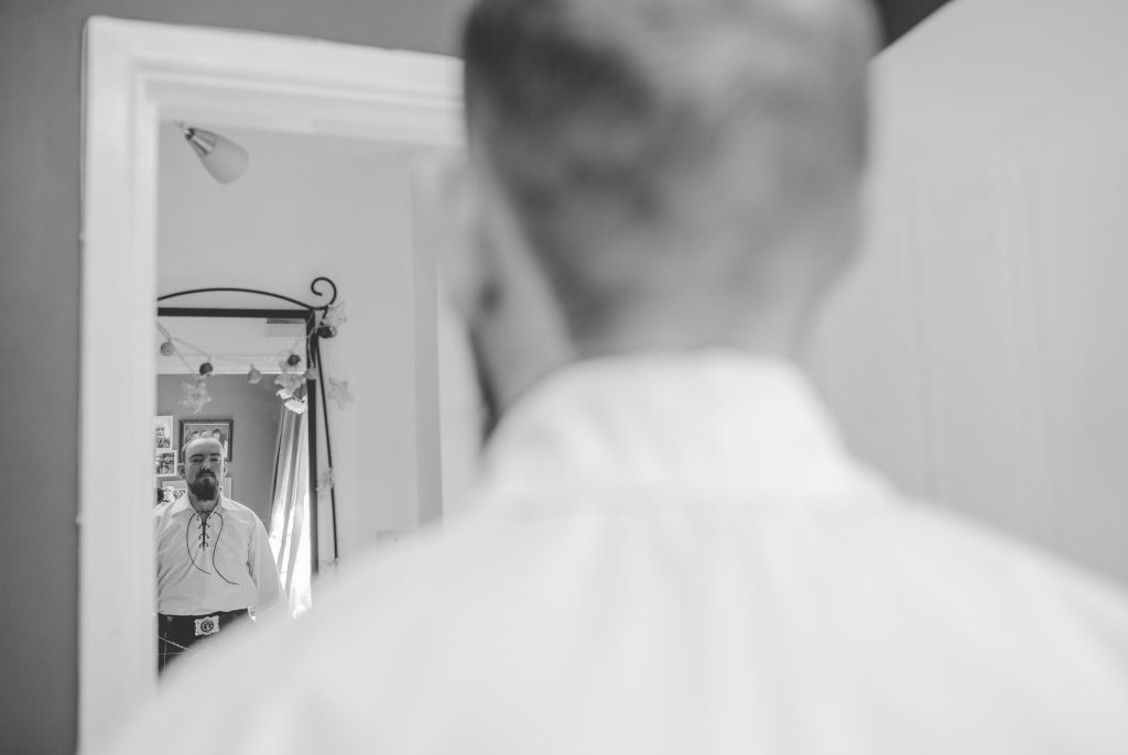 black and white photo of groom looking in mirror