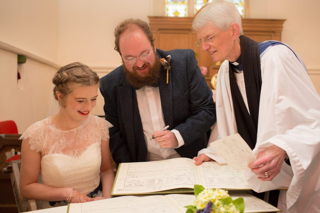Bride and groom with vicar signing register
