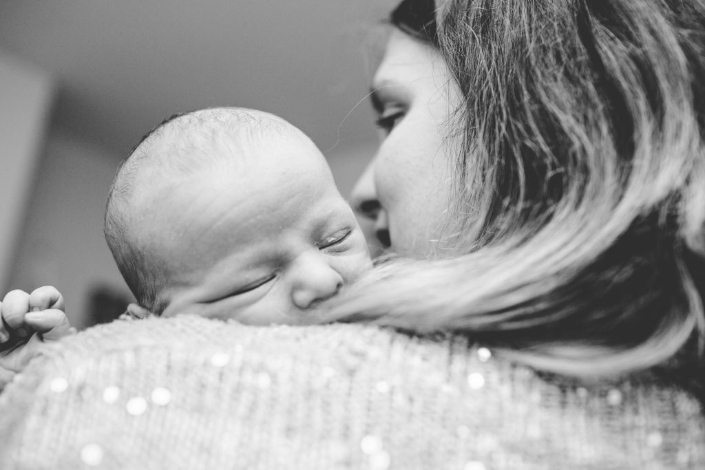 black and white photo of baby over mums shoulder