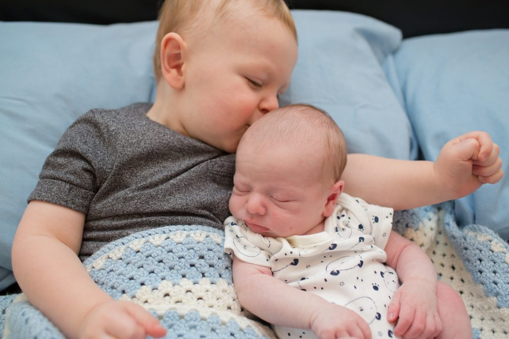 young child kissing baby brother on head