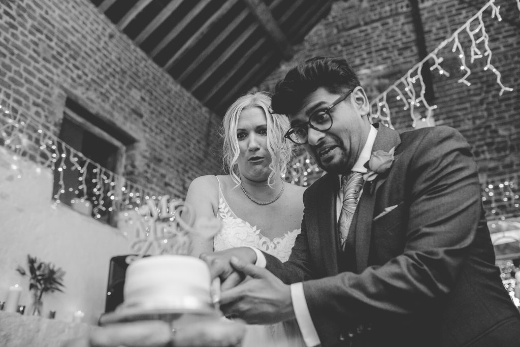 black and white photo of newly weds cutting cake
