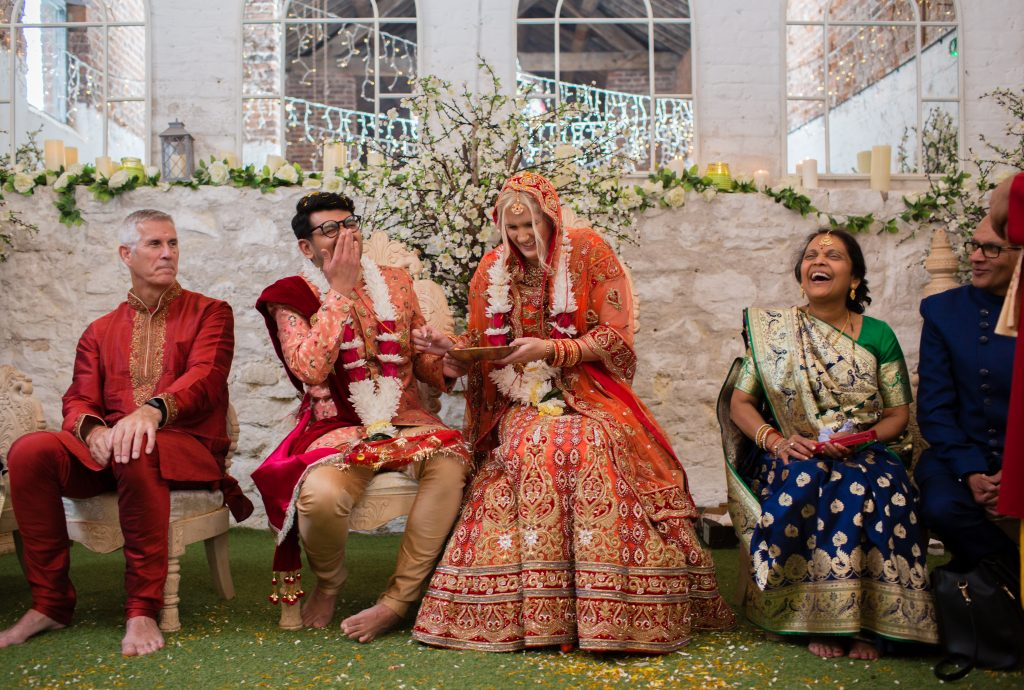 bride and groom laugh during hindu wedding ceremony