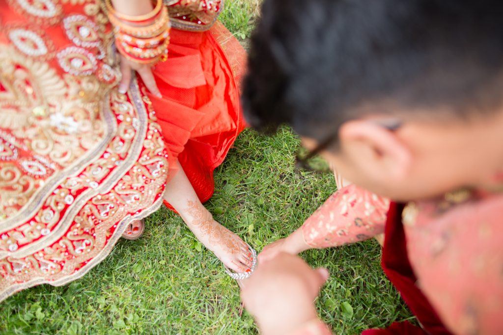 groom looking at henna on brides foot