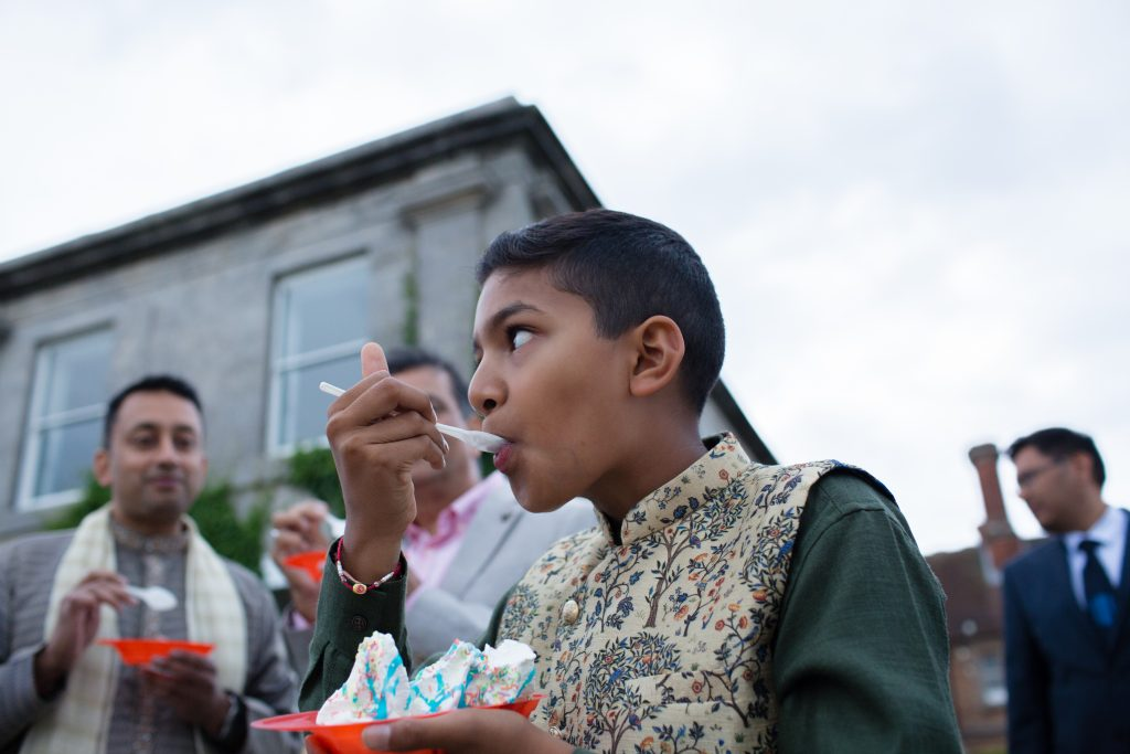 young wedding guest eating icecream