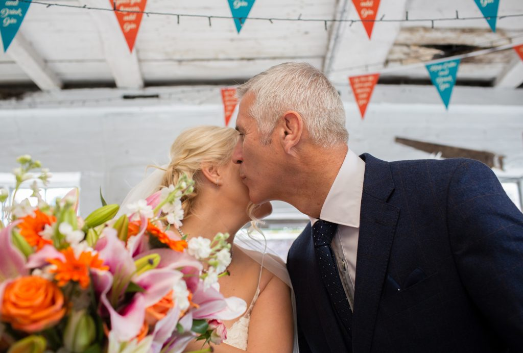 father of bride kissing daughter on cheek