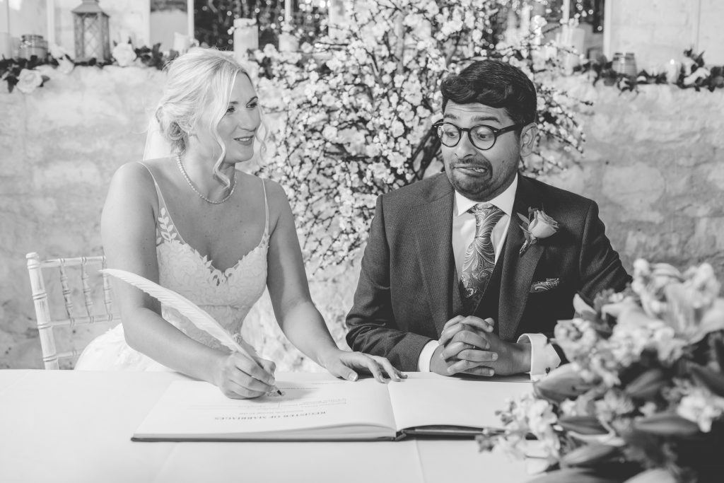 black and white photo of couple signing wedding register