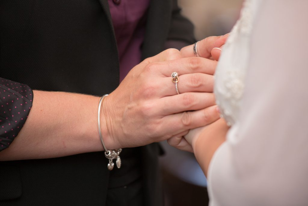 close up picture of maid of honour holding brides hands