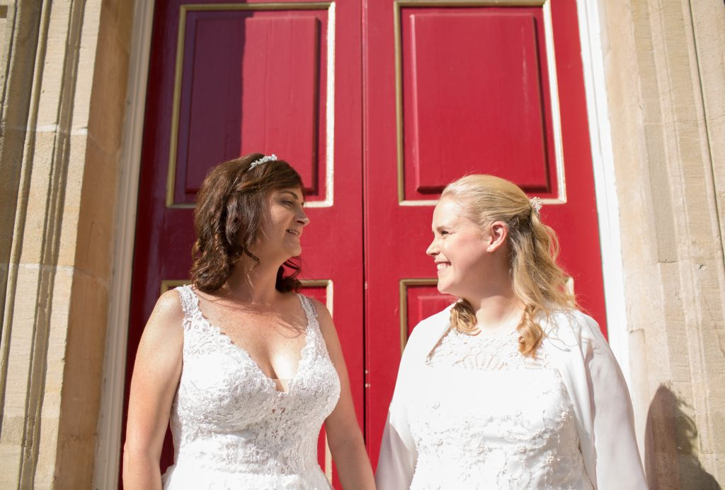 two brides stand outside red door at windsor guildhall