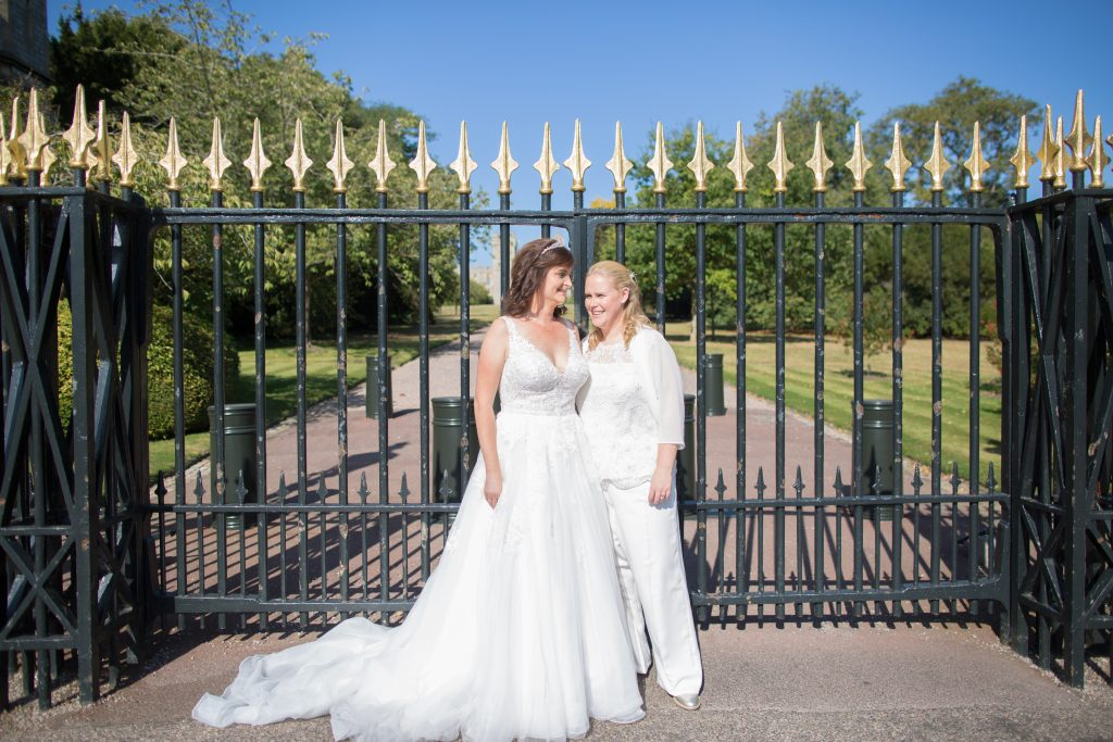 two brides stood in front of gates at windsor castle