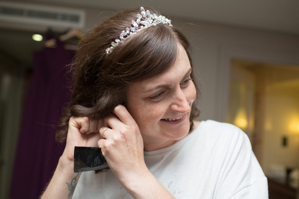 photography of bride putting earrings in