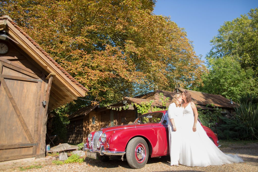 two brides standing in front of classic wedding car