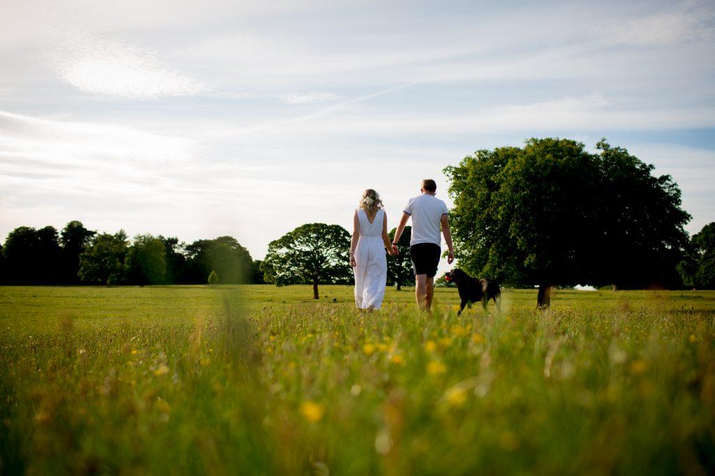 couple walking through feild with dog
