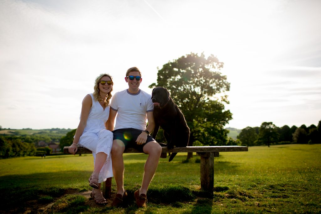couple sat on bench with dog