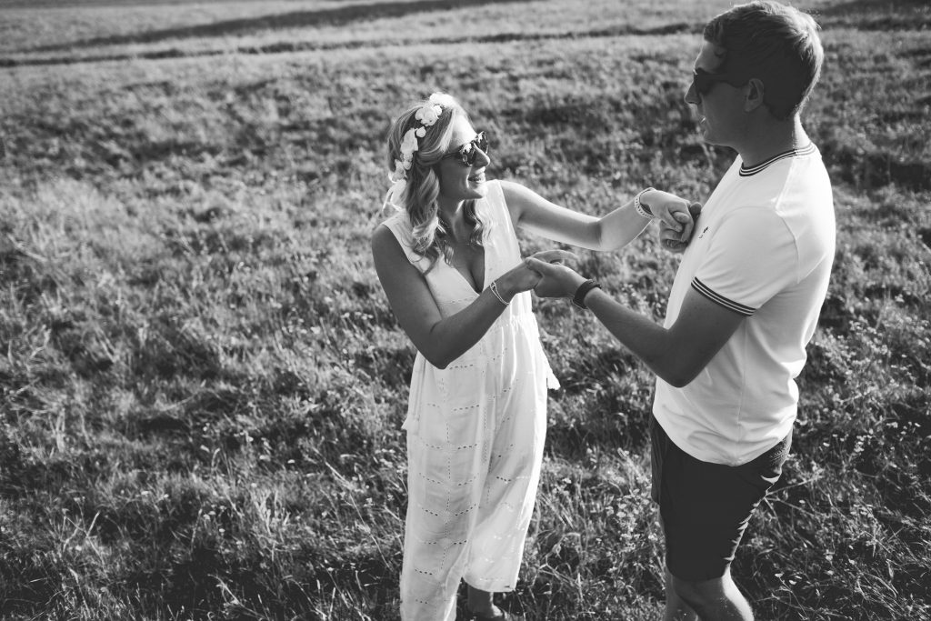 black and white photo of couple dancing in feild