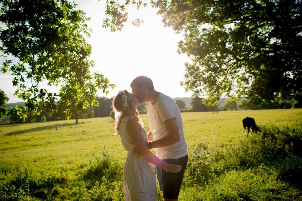 couple kiss under trees